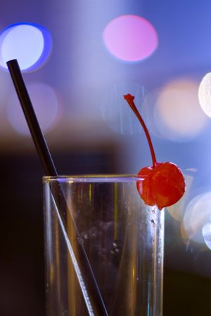 Empty cocktail glass with cherry and coloured lights behind