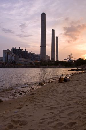 Power station at sunset beach in foreground