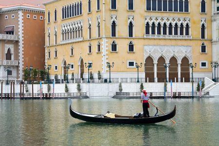 Gondolier navigates the venetian canal Stock Photo
