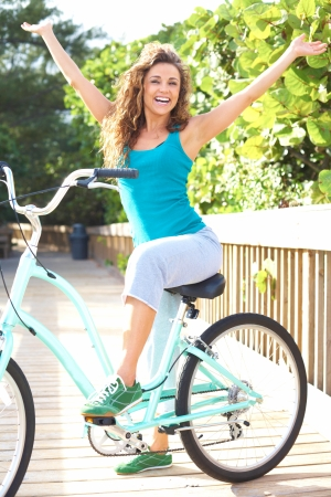 Full length portrait of carefree young woman sitting on bicycle with arms out. Vertical shot. photo
