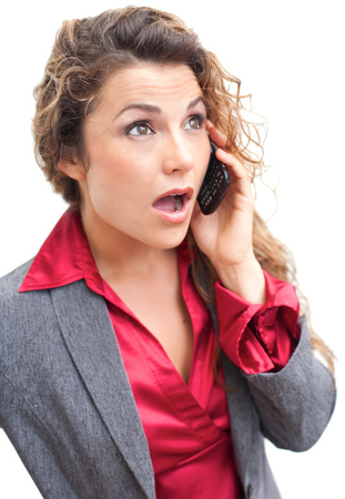 Beautiful business woman talking on cellphone in shock photo