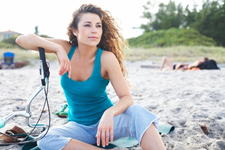 liesure: beautiful girl at the beach with bicycle looking out at the ocean Stock Photo
