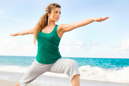Beautiful female doing yoga warrior pose at the beach with copy space photo