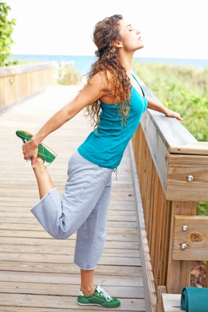 beautiful girl on boardwalk stretching photo