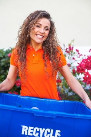 recycling bin: pretty woman holding recycle bin smiling