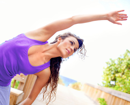 young beautiful girl stretching at the beach keeping fit on the boardwalk photo