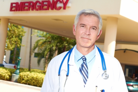Portrait of a confident mature doctor with emergency sign in background. Horizontal shot. photo