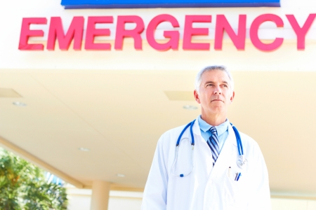 Confident mature doctor looking away with emergency sign in background. Horizontal shot. photo