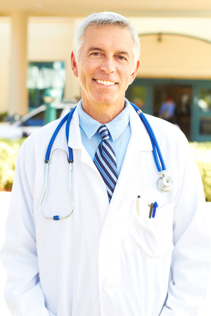 Portrait of a mature medical professional smiling with building in background. Vertical shot. photo