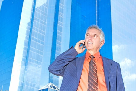 Mature businessman in front of an office building talking on cell phone. Horizontal shot. photo
