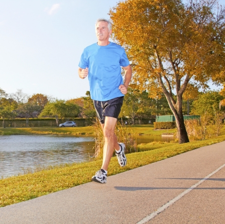 body concern: Full length of a mature man jogging with fountain in background. Horizontal shot. Stock Photo