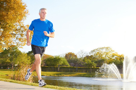 and the horizontal man: Full length of a mature man jogging with fountain in background. Horizontal shot. Stock Photo