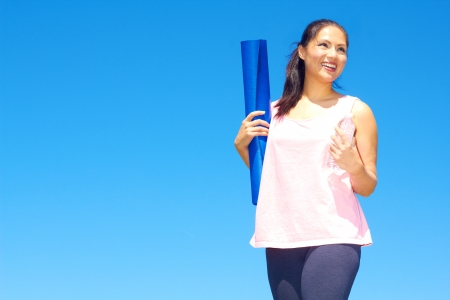young beautiful mixed race girl holding yoga mat and bottle of water on a nice spring day. Color image, copy space. photo