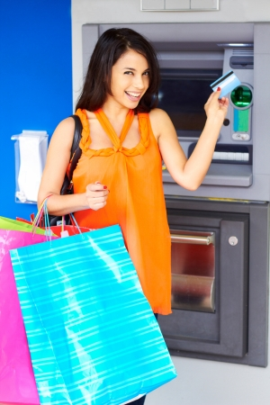 Portrait of a cheerful young woman with multi colored shopping bags and debit card. Vertical shot. photo