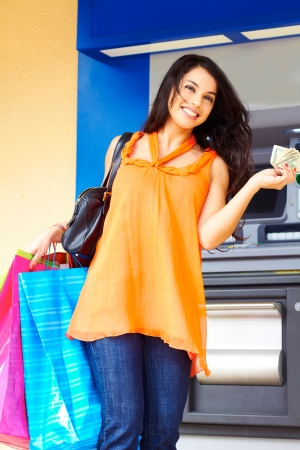 Portrait of cheerful young woman with multi colored shopping bags holding cash in hand. Vertical shot. photo