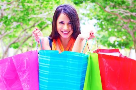 Beautiful young woman smiling while carrying shopping bags. Horizontal Shot. photo