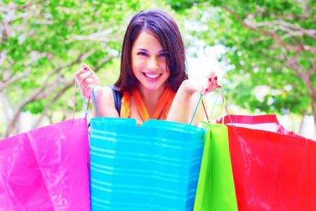 Beautiful young woman smiling while carrying shopping bags. Horizontal Shot. Stock Photo - 23575966