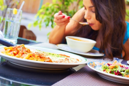 forground: Woman eating minnestrone vegetable soup with chicken parmesan in the forground. Pretty female blowing on hot soup. Focus on pasta dish in foreground. Stock Photo