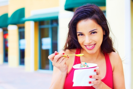 Portrait of a happy smiling young hispanic woman enjoying frozen yogurt at cafe table. Horizontal shot. photo