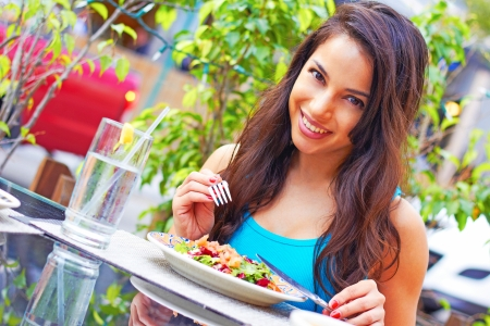 Portrait of a young attractive woman eating salad at cafe table. Horizontal shot. photo