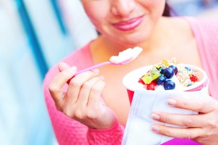 yogur: Hembra mestiza muy joven bastante feliz que come yogurt congelado mientras se mira lejos. Tiro horizontal.