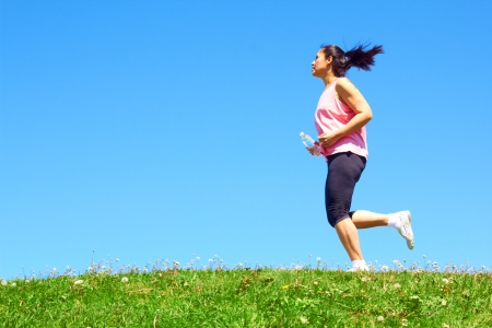 Sporty mixed race woman jogging. Color image, copy space, asian ethnicity female running with green grass and blue sky. photo