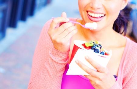 yaourt: Tr�s heureux jeune femme jolie course mixte de manger du yogourt glac� tout en regardant loin. Prise de vue horizontale.