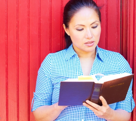 reading bible: Pretty young mixed race woman in casual wear reading holy bible.