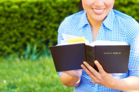 Pretty young mixed race woman in casual wear reading holy bible. photo