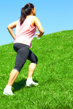 Sporty mixed race woman jogging. Color image, copy space, asian ethnicity female running uphill with green grass and blue sky. photo