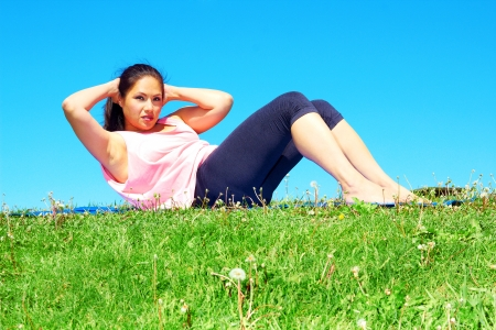 young beautiful mixed race girl doing sit ups on a beautiful day with clear blue sky. Pretty asian female performing relaxation exercise on a nice spring day. Color image, copy space. photo