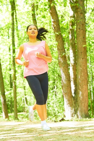 Sporty mixed race woman jogging. Color image, copy space, asian ethnicity female running in forest photo