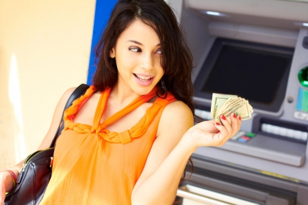 machine: Beautiful young woman holding cash with ATM machine in background. Horizontal shot.