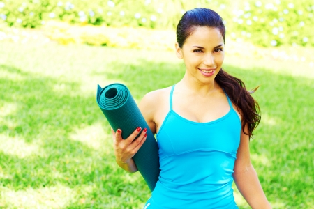 Beautiful happy hispanic female holding yoga mat with copy space photo