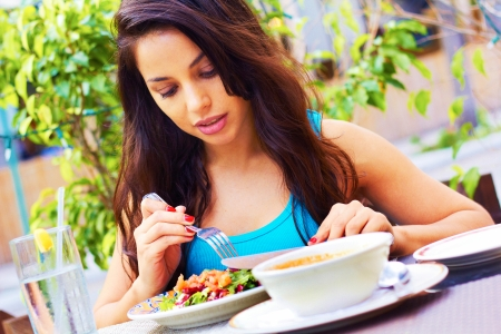 Portrait of young woman having fresh salad at outdoors restaurant.  photo