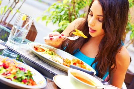 restuarant: Portrait of a beautiful young woman eating chicken parmesan at restuarant.  Stock Photo