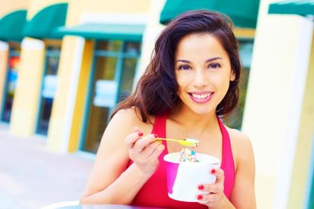 frozen yogurt: Portrait of a happy smiling young hispanic woman enjoying frozen yogurt at cafe table. Horizontal shot.