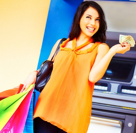 Portrait of cheerful young woman with multi colored shopping bags holding cash in hand. photo