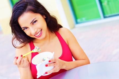 Portrait of a happy smiling young hispanic woman enjoying frozen yogurt at cafe table. Horizontal shot. photo