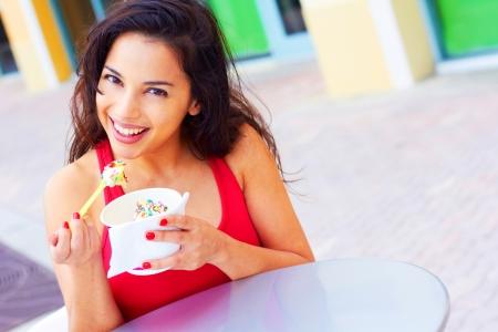 yaourt: Portrait d'une jeune femme heureuse en appr�ciant yogourt glac� � la table de caf�. Prise de vue horizontale.