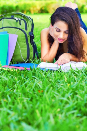 Young woman reading a book while lying on grass. Vertical shot. photo
