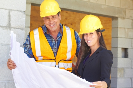 construction manager: Architect and foreman reviewing blueprint together at construction site. Stock Photo