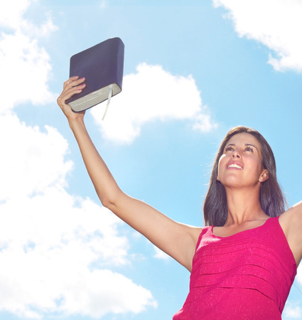 Beautiful young female celebrating success with a Bible against cloudy sky. Horizontal Shot. photo
