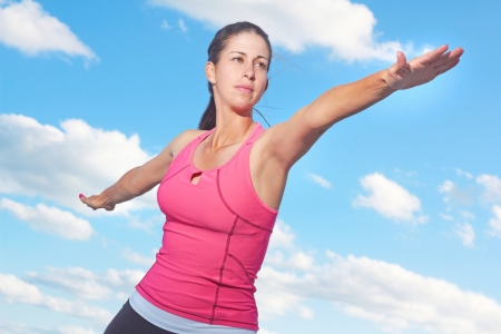 body concern: Healthy young woman doing yoga warrior pose against cloudy sky. Horizontal Shot.