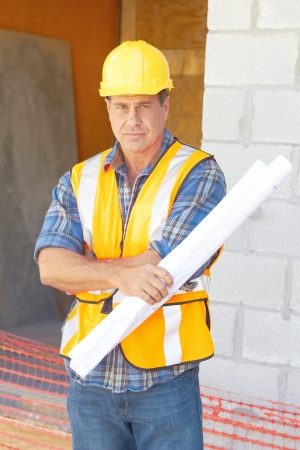 Portrait of a serious building contractor with blueprints at construction site. Vertical shot. photo