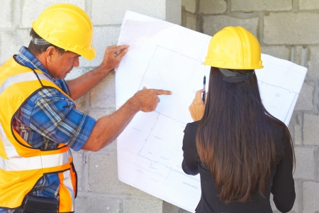 Architect and foreman reviewing blueprint together at construction site. photo