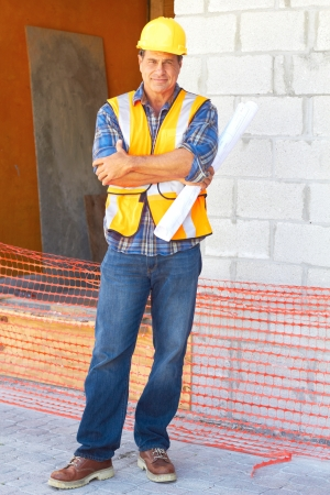 Full length portrait of a building contractor with blueprints at construction site. Vertical shot. photo