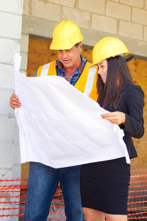 architecture plans: Architect and foreman reviewing blueprint together at construction site. Stock Photo
