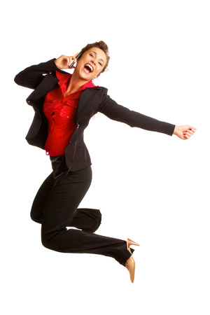 Beautiful caucasian business female jumping for with joy on cellphone isolated on white. photo