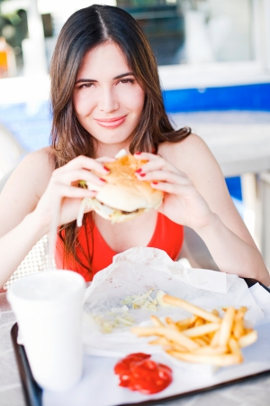 Beautiful happy young latin girl eating hamburger at fast food restuarant photo